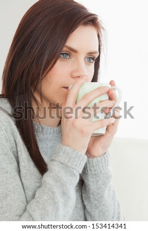 Thinking brunette drinking a cup of coffee at home - stock photo