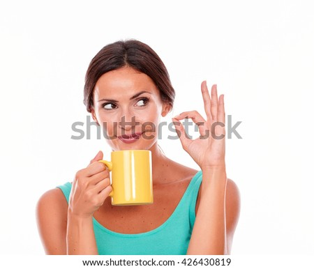 Thinking brunette woman with coffee mug looking away gesturing a perfect sign and wearing a green tank top and her long hair tied back isolated - stock photo