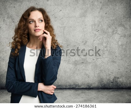 Thinking business woman looking up isolated on gray background - stock photo