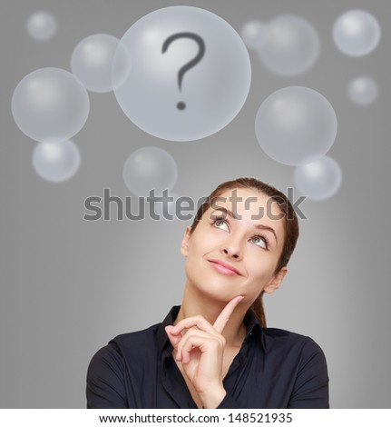 Thinking business woman looking up on many bubbles with question mark on grey background - stock photo