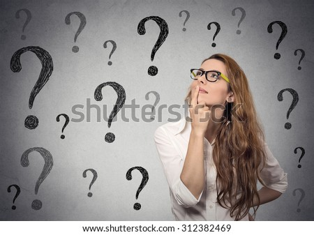 Thinking business woman with glasses looking up on many questions mark isolated on gray wall background