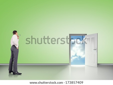 Thinking businessman holding glasses against clouds over maze
