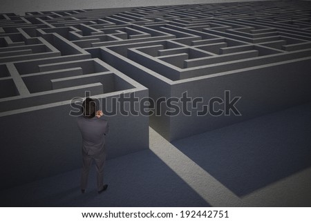 Thinking businessman holding pen against entrance to difficult maze puzzle
