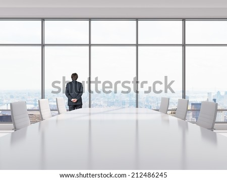 Thinking businessman in a Conference room. Modern office with windows and city view.  - stock photo