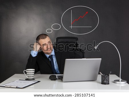 Thinking businessman in office and line graph   - stock photo