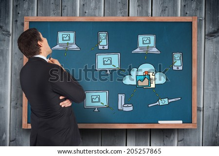 Thinking businessman looking at technology doodles on board - stock photo