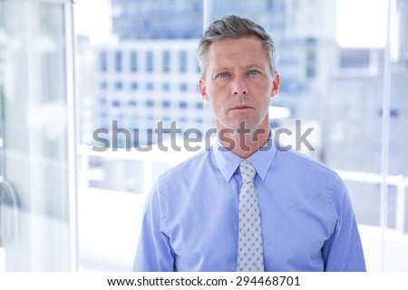 Thinking businessman looking at the camera in the office - stock photo