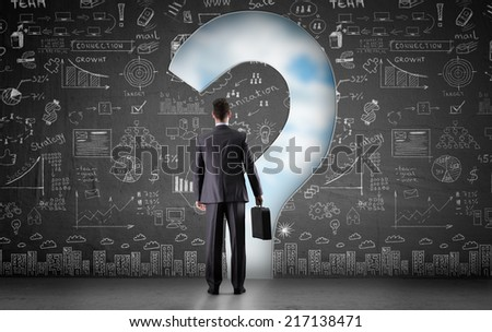 thinking businessman looks through a hole in wall in in the form of a question mark - stock photo
