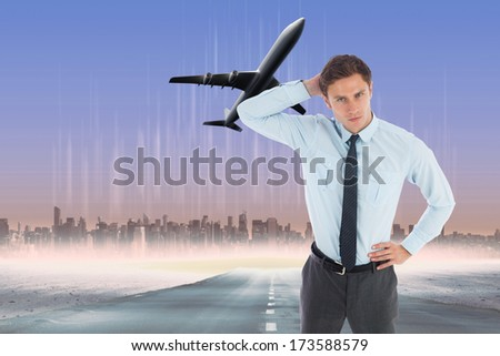 Thinking businessman scratching head against cityscape on the horizon