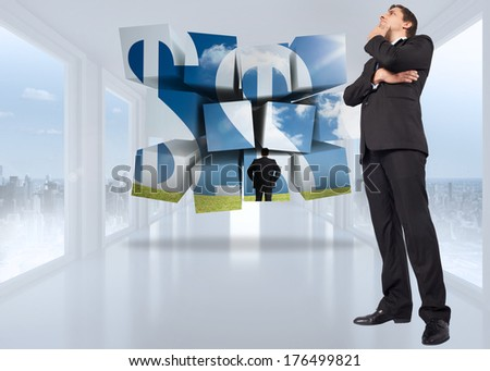 Thinking businessman touching chin against bright white hall with windows