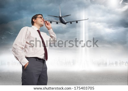 Thinking businessman touching his glasses against city on the horizon with light beam