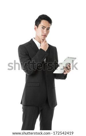 Thinking businessman using a tablet - stock photo
