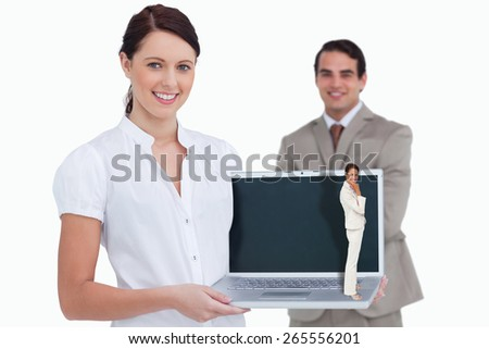 Thinking businesswoman against smiling saleswoman presenting laptop screen with colleague behind her