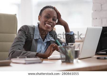 Thinking businesswoman in suit sitting at workplace and working hard with laptop - stock photo