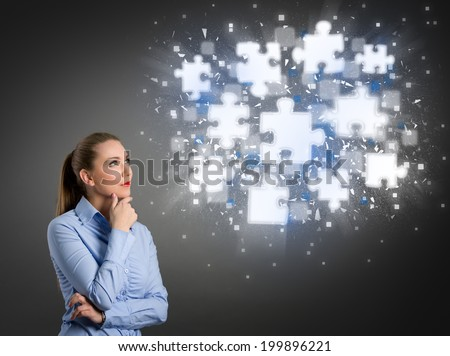 Thinking businesswoman looking at clouds of shining puzzle pieces - stock photo