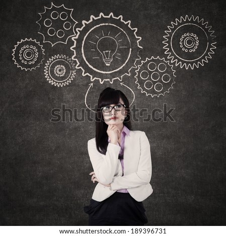 Thinking businesswoman with mechanisms on the blackboard - stock photo