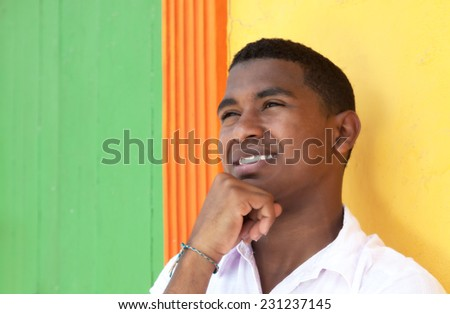 Thinking caribbean guy in front of a colorful wall - stock photo