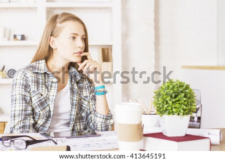 Thinking caucasian female with hand at chin sitting at office desk with various items  - stock photo