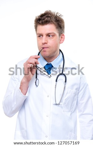 Thinking cheerful male doctor with stethoscope and glasses in his hand