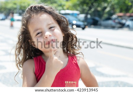 Thinking child in a red shirt outside in the city in summer - stock photo