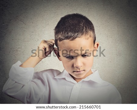 Thinking child, scratching back of his head isolated grey wall background. Human face expressions, emotions, body language - stock photo