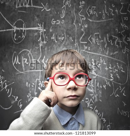 Thinking child with a blackboard in the background - stock photo