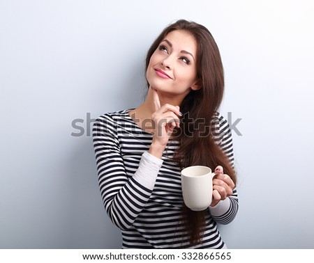 Thinking concerned young woman looking up with cup of coffee on blue background - stock photo