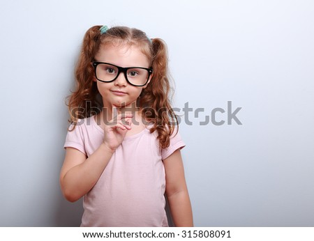 Thinking cute kid girl looking confident in eyeglasses on blue background - stock photo