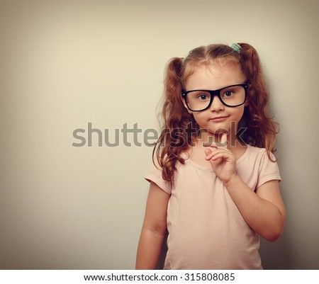 Thinking cute kid girl looking confident in eyeglasses. Vintage portrait with empty copy space - stock photo