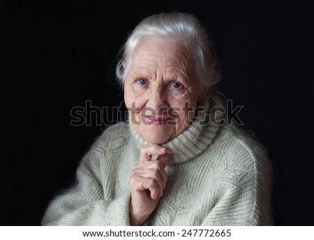 Thinking elderly woman portrait - stock photo