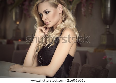 thinking elegant girl in black , with curly hair sitting at the restaurant bar waiting . old fashion style - stock photo