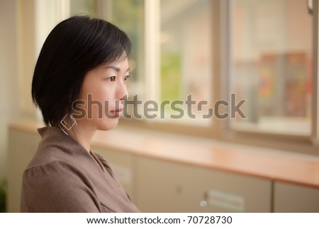 Thinking expression of Asian mature woman, closeup portrait indoor.