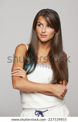 Thinking funky young female with blue hair lock standing with folded hands and looking away, over gray background - stock photo