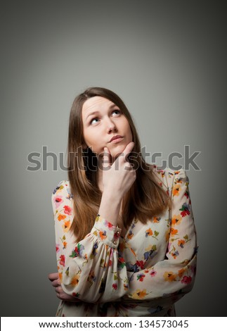 Thinking. Girl full of doubts and hesitation - stock photo