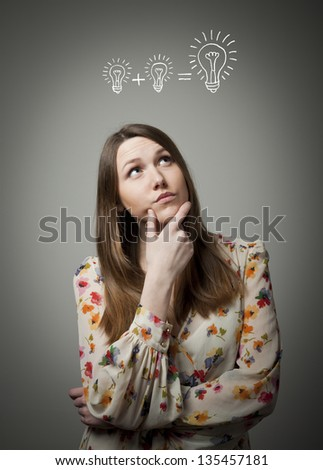 Thinking. Girl having an idea with light bulb over her head. - stock photo
