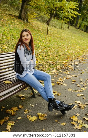 Thinking girl sitting on park seat
