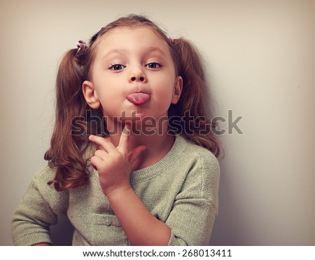 Thinking grimacing girl showing tongue with finger under face and looking funny in camera. Vintage closeup portrait - stock photo