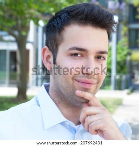 Thinking hispanic guy in a blue shirt  - stock photo