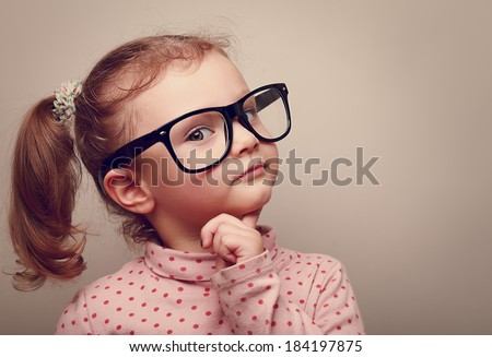 Thinking kid girl in glasses looking happy. Closeup instagram effect portrait - stock photo