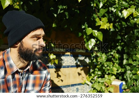 Thinking man by green plans . Multiracial hipster university college student pensive and contemplating looking into the distance at green plants background. Asian Caucasian, 20s. - stock photo