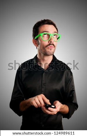 thinking man holding phone on gray background