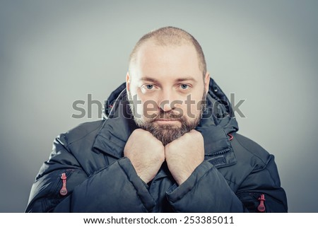 Thinking man isolated on gray background. Close-up portrait of a beautiful young thoughtful man. - stock photo