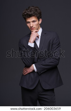 Thinking man isolated on gray background.Young pensive businessman looking down with hand on chin. Caucasian male model. - stock photo