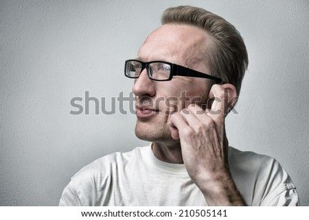 Thinking man on gray textured background. Closeup portrait of a casual young pensive businessman looking up at copy space and itch his ear.  - stock photo