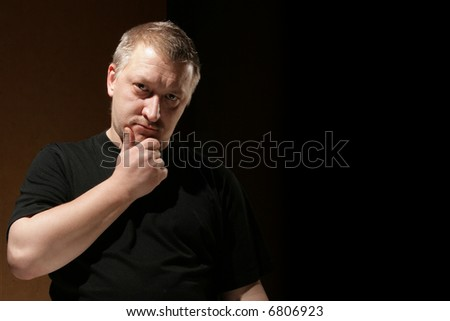 Thinking man over dark background with space for text on right - stock photo