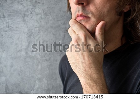 Thinking man with hand on his chin looking back to his past actions - stock photo