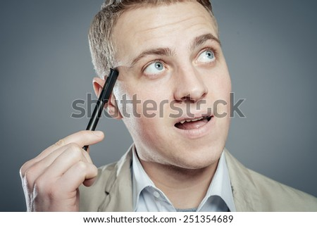 Thinking man with pen near his face isolated on gray background. Closeup portrait of a casual young pensive businessman looking up at copyspace. - stock photo