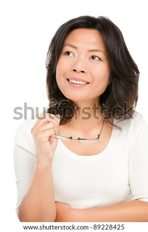 Thinking middle aged mature Asian woman looking up at copy space. Pensive mid age Chinese asian woman in her early 50s isolated on white background. - stock photo