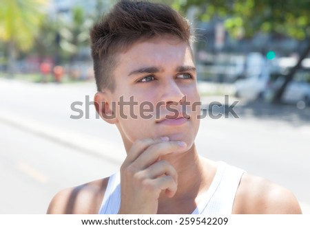 Thinking muscular guy in the city - stock photo