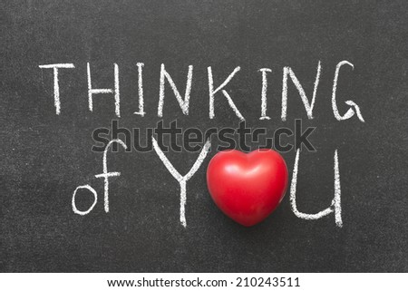 thinking of you phrase handwritten on blackboard with heart symbol instead of O